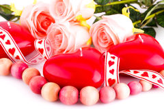 Red heart candles, necklace and roses. Red heart candles, wooden necklace, ribbon and roses on white background Stock Images