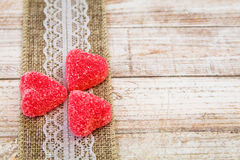 Red heart candy and burlap lace on wooden board stock photography