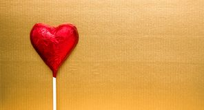 Red heart candy on gold Royalty Free Stock Photos