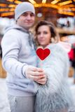 Red heart candy on a stick in the hands of young couple in love at the Christmas fair royalty free stock photo