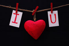 Red heart and card text I LOVE YOU holds on on wooden cloth pegs on a rope. On a black background. Festive romantic image for Valentine's Day Stock Images