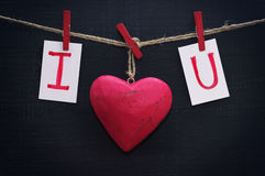 Red heart and card text I LOVE YOU holds on on wooden cloth pegs on a rope. On a black wooden background. Festive romantic image for Valentine's Day Royalty Free Stock Images
