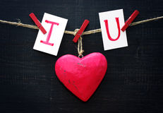 Red heart and card text I LOVE YOU holds on on wooden cloth pegs on a rope. On a black wooden background. Festive romantic image for Valentine's Day Royalty Free Stock Photography