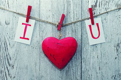 Red heart and card text I LOVE YOU holds on on wooden cloth pegs on a rope. On old wooden background. Festive romantic image for Valentine's Day Royalty Free Stock Images