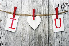 Red heart and card text I LOVE YOU holds on on wooden cloth pegs on a rope. Paper heart and card text I LOVE YOU holds on on wooden cloth pegs on a rope on a Royalty Free Stock Image