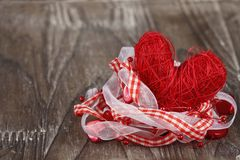 Red heart with checkered ribbon. On wooden background Stock Images