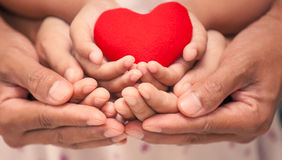 Red heart in child kid  mother and father hands. In vintage color tone. love,care and family concept Stock Photo