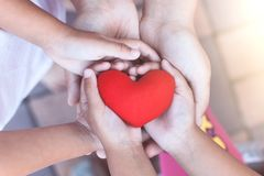 Red heart in child and parent hands with love and harmony. Family holding red heart together royalty free stock photos