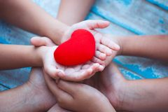 Red heart in child and parent hands with love and harmony. Family holding red heart together royalty free stock images