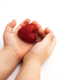 Red heart in the children's arm Stock Image