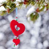 Red heart christmas ornament outdoor winter forest. Single red heart shaped Christmas or Valentines decoration hanging from snow covered branches of pine tree in Stock Photo