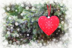 Red heart on christmas tree. As holiday decoration with white illustrated snowflakes. Merry christmas and happy new year greeting card royalty free stock photo