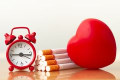 Red heart and cigarettes. Smoking cigarette destroying health. stock photo