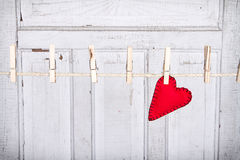 Heart on a clothes line. Red heart on a clothes line with a weathered white vintage panel in the background Stock Photography