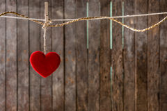 Red heart with clothespin hanging on clothesline. Wooden background Stock Photography