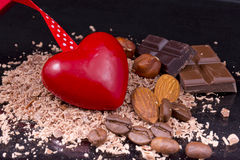 Red heart with coffee beans, chocolate, almonds and hazelnuts Royalty Free Stock Photography
