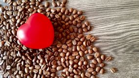 Red heart and coffee grains. On wooden background Stock Images
