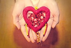 Red heart of colored beads in hands royalty free stock images