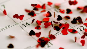Red heart confetti falling on calendar. In slow motion stock footage