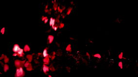 Red heart confetti falling down on black background. In slow motion stock footage