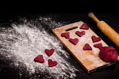 Red heart cookie and a piece of dough on the wooden board, baking for Valentine's Day Stock Photo