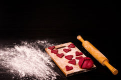 Red heart cookie and a piece of dough on the wooden board, baking for Valentine's Day Royalty Free Stock Photos