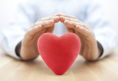 Red heart covered by hands royalty free stock photo