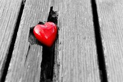 Red heart in crack of wooden plank. Symbol of love Stock Image