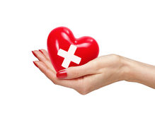 Red heart with cross sign in woman hand, isolated on white. Background Stock Image