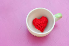 Red heart in cup. Red heart in the coffee cup on pink table Stock Photography