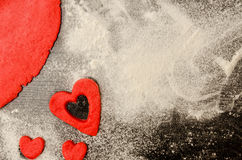 Red heart cut out of the dough on the flour, black table, space for text Royalty Free Stock Images
