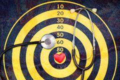 Red heart on dartboard with crack and stethoscope stock photography