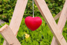 Red heart decoration hanging on wood Stock Photos