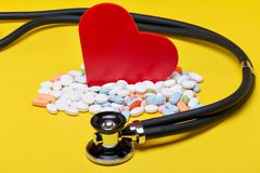 Red heart with different pills an stethoscope. With yellow background stock images