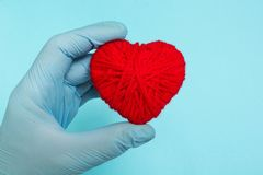 Red heart in the doctor`s hand on a blue background, concept royalty free stock image
