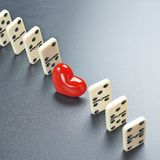 Red heart between the domino pieces Stock Images
