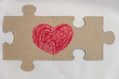 Red heart is drawn on the pieces of the puzzle lying next to each other Stock Image