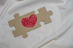 Red heart is drawn on the pieces of the puzzle lying next to each other stock photo