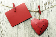 Red heart and empty red card with place for text on wooden cloth pegs on the clothesline Royalty Free Stock Photo
