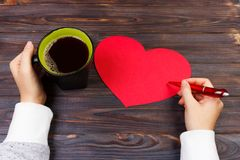 Red heart envelope on a wooden table in the office. Love letter, Valentines card, holiday letter gift and cup of coffee on office. Desk Royalty Free Stock Images