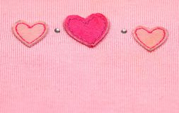 Red heart in fabric. Old cloth details with fabric hearts Royalty Free Stock Photo