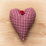 Red heart of fabric. On a wooden background Stock Images