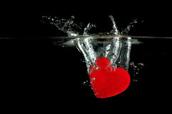 Red heart falling on water splashing. Stock Photography