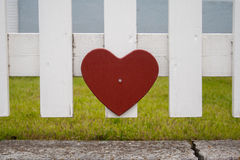 Red heart on a fence. A red heart on a white fence Stock Photos