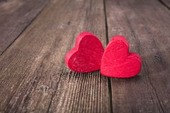 Red heart figures over vintage wooden background royalty free stock image