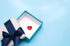 red heart figurine with a smile in a gift box