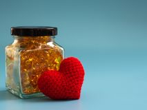 Red heart beside Fish oil capsules in glass bottles on blue background. Healthy omega-3 and stethoscope.  royalty free stock images