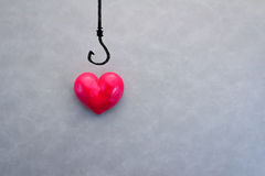 Red heart on a fishing hook. With copy-space love trap concept stock photos