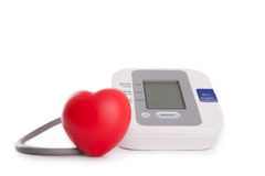 red heart in front of blood pressure meter Royalty Free Stock Photos