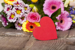 Red heart in front of a Bouquet Royalty Free Stock Images